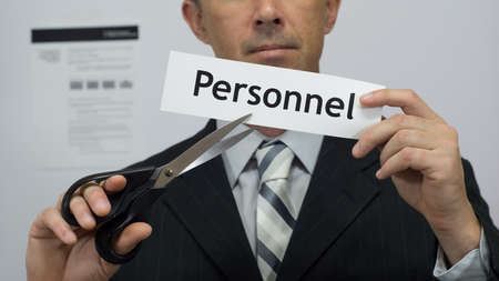 Male office worker or businessman in a suit and tie cuts a piece of paper with the word personnel on it as a personnel reduction business concept. Stock Photo