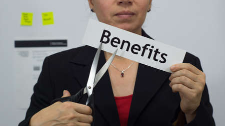 Female office worker or business woman cuts a piece of paper with the word benefits on it as a benefits reduction business concept.