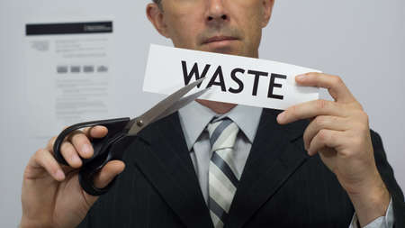Male office worker or businessman in a suit and tie cuts a piece of paper with the word waste on it as a waste reduction business concept. Stock Photo