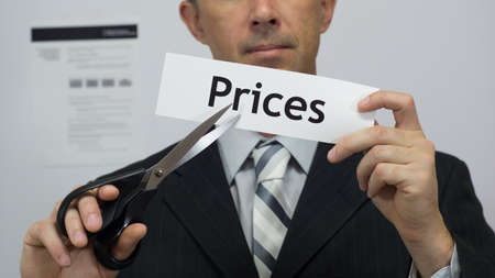 Male office worker or businessman in a suit and tie cuts a piece of paper with the word prices on it as a price reduction business concept. Stock Photo
