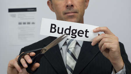 Male office worker or businessman in a suit and tie cuts a piece of paper with the word budget on it as a cutting budget reduction business concept.