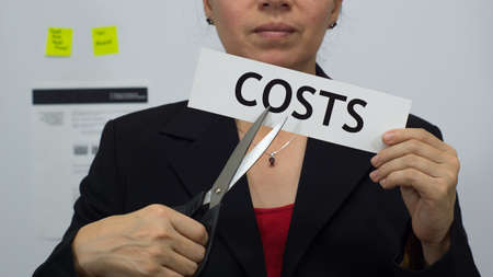 streamlining: Female office worker or business woman cuts a piece of paper with the word costs on it as a cost reduction business concept. Stock Photo
