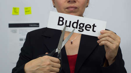 Female office worker or business woman cuts a piece of paper with the word budget on it as a cutting budget reduction business concept.