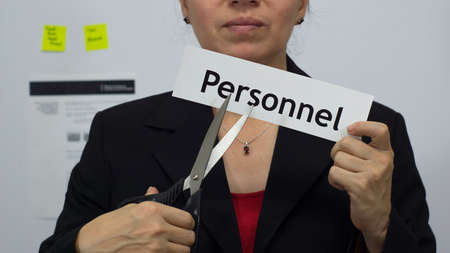 Female office worker or business woman cuts a piece of paper with the word personnel on it as a personnel reduction business concept.