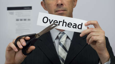 Male office worker or businessman in a suit and tie cuts a piece of paper with the word overhead on it as an overhead reduction business concept. Stock Photo