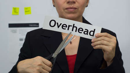 Female office worker or business woman cuts a piece of paper with the word overhead on it as an overhead reduction business concept. Stock Photo