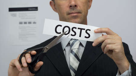 Male office worker or businessman in a suit and tie cuts a piece of paper with the word costs on it as a cost reduction business concept. Stock Photo