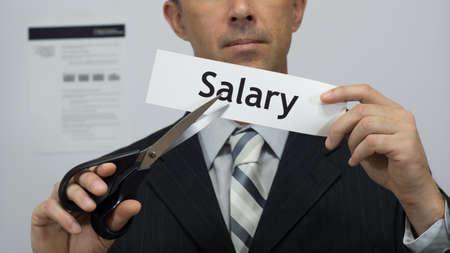 employé de bureau Homme ou d'affaires dans un costume et une cravate coupe un morceau de papier avec le mot salaire sur elle comme un concept d'entreprise salaire ou une réduction de salaire. Banque d'images