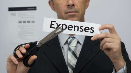 Male office worker or businessman in a suit and tie cuts a piece of paper with the word expenses on it as an expense reduction business concept.