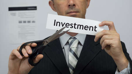Male office worker or businessman in a suit and tie cuts a piece of paper with the word investment on it as an investment reduction business concept.