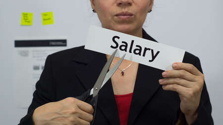 Female office worker or business woman cuts a piece of paper with the word salary on it as a salary or pay reduction business concept. Stock Photo