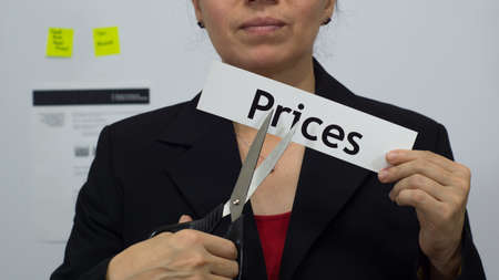 Female office worker or business woman cuts a piece of paper with the word prices on it as a price reduction business concept.