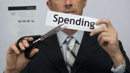 Male office worker or businessman in a suit and tie cuts a piece of paper with the word spending on it as a spending or expense reduction business concept. Stock Photo