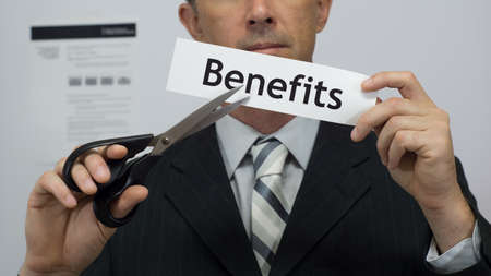 Male office worker or businessman in a suit and tie cuts a piece of paper with the word benefits on it as a benefits reduction business concept. Stock Photo