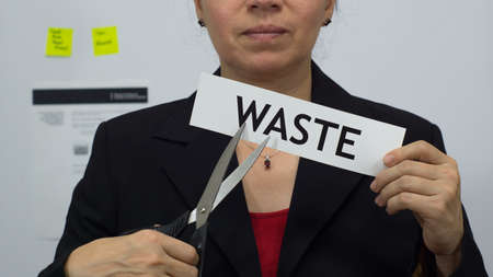 Female office worker or business woman cuts a piece of paper with the word waste on it as a waste reduction business concept.