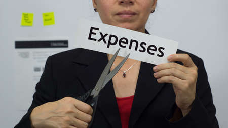 Female office worker or business woman cuts a piece of paper with the word expenses on it as an expense reduction business concept.