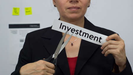 Female office worker or business woman cuts a piece of paper with the word investment on it as an investment reduction business concept.
