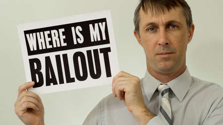 Middle aged man wearing a dress shirt and tie holds up a sign that asks where his bailout is which refers to his financial situation and bankruptcy.