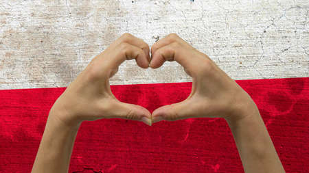 With a stylized Polish flag background an anonymous persons hands being held in the form of a heart, symbolizing love and patriotism for Poland.