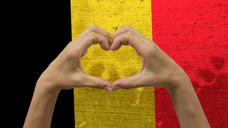 With a stylized Belgian flag background an anonymous persons hands being held in the form of a heart, symbolizing love and patriotism for Belgium.