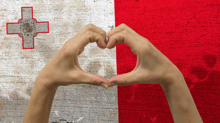 With a stylized Maltese flag background an anonymous persons hands being held in the form of a heart, symbolizing love and patriotism for Malta. Stock Photo