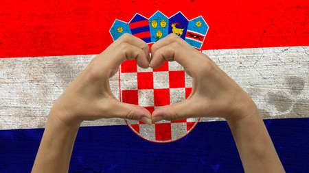 With a stylized Croatian flag background an anonymous persons hands being held in the form of a heart, symbolizing love and patriotism for Croatia.