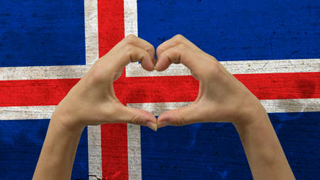 With a stylized Icelandic flag background an anonymous persons hands being held in the form of a heart, symbolizing love and patriotism for Iceland.