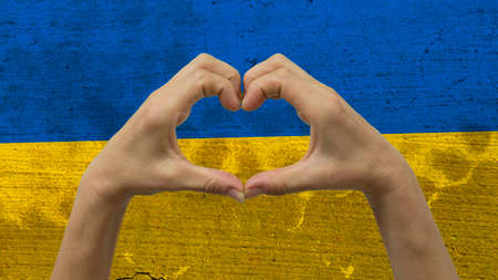 With a stylized Ukrainian flag background an anonymous persons hands being held in the form of a heart, symbolizing love and patriotism for Ukraine.