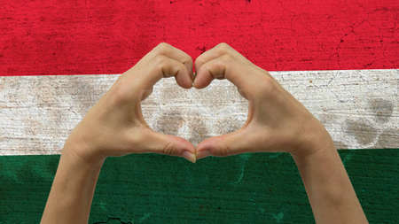 With a stylized Hungarian flag background an anonymous persons hands being held in the form of a heart, symbolizing love and patriotism for Hungary.