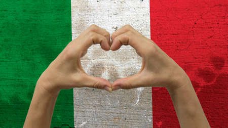 With a stylized Italian flag background an anonymous persons hands being held in the form of a heart, symbolizing love and patriotism for Italy.