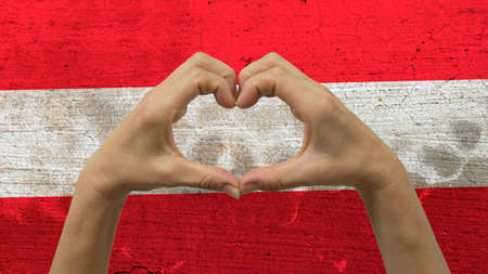 With a stylized Austrian flag background an anonymous persons hands being held in the form of a heart, symbolizing love and patriotism for Austria.