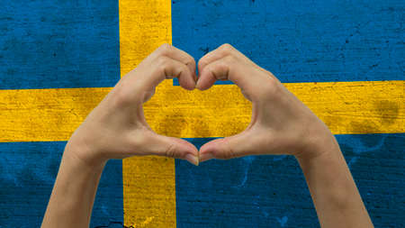 With a stylized Swedish flag background an anonymous persons hands being held in the form of a heart, symbolizing love and patriotism for Sweden. Stock Photo