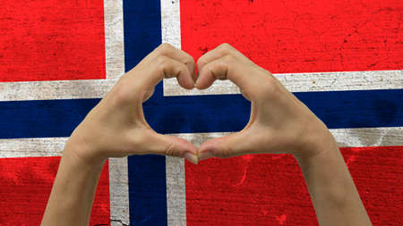With a stylized Norwegian flag background an anonymous persons hands being held in the form of a heart, symbolizing love and patriotism for Norway.