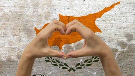 With a stylized Cypriot flag background an anonymous persons hands being held in the form of a heart, symbolizing love and patriotism for Cyprus.