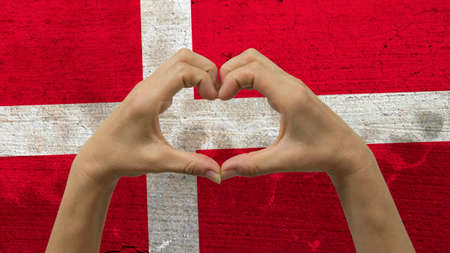 With a stylized Danish flag background an anonymous persons hands being held in the form of a heart, symbolizing love and patriotism for Denmark.