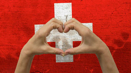 With a stylized Swiss flag background an anonymous persons hands being held in the form of a heart, symbolizing love and patriotism for Switzerland. Stock Photo