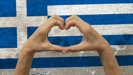 With a stylized Greek flag background an anonymous persons hands being held in the form of a heart, symbolizing love and patriotism for Greece.