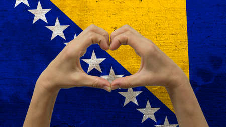 nationalistic: With a stylized Bosnian flag background an anonymous persons hands being held in the form of a heart, symbolizing love and patriotism for Bosnia and Herzegovina. Stock Photo