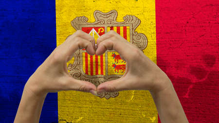 With a stylized Andorran flag background an anonymous persons hands being held in the form of a heart, symbolizing love and patriotism for Andorra.