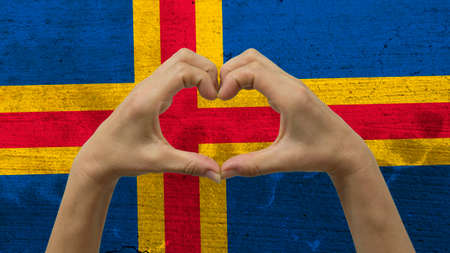 With a stylized Alandic flag background an anonymous persons hands being held in the form of a heart, symbolizing love and patriotism for Aland Islands.