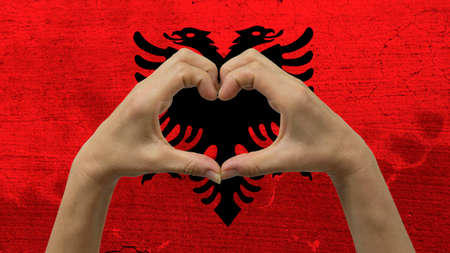 With a stylized Albanian flag background an anonymous persons hands being held in the form of a heart, symbolizing love and patriotism for Albania. Stock Photo
