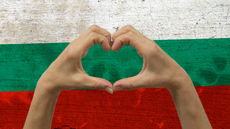 With a stylized Bulgarian flag background an anonymous persons hands being held in the form of a heart, symbolizing love and patriotism for Bulgaria.