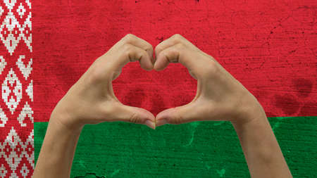 With a stylized Belarusian flag background an anonymous persons hands being held in the form of a heart, symbolizing love and patriotism for Belarus. Stock Photo
