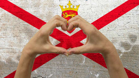 With a stylized Jersey flag background an anonymous persons hands being held in the form of a heart, symbolizing love and patriotism for Jersey