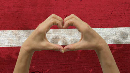 With a stylized Latvian flag background an anonymous persons hands being held in the form of a heart, symbolizing love and patriotism for Latvia. Stock Photo