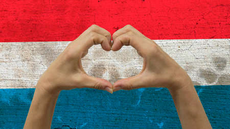 With a stylized Luxembourgish flag background an anonymous persons hands being held in the form of a heart, symbolizing love and patriotism for Luxembourg. Stock Photo