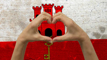 With a stylized Gibraltarian flag background an anonymous persons hands being held in the form of a heart, symbolizing love and patriotism for Gibraltar.