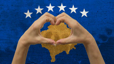 With a stylized Kosovan flag background an anonymous persons hands being held in the form of a heart, symbolizing love and patriotism for Kosovo.