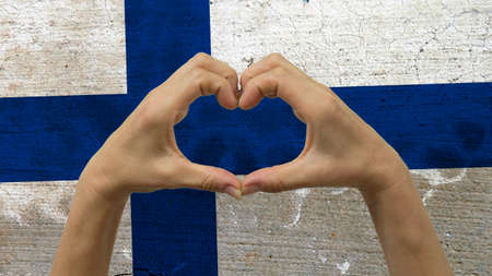 With a stylized Finnish flag background an anonymous persons hands being held in the form of a heart, symbolizing love and patriotism for Finland.
