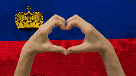 With a stylized Liechtensteinan flag background an anonymous persons hands being held in the form of a heart, symbolizing love and patriotism for Liechtenstein.